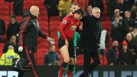 Bek Manchester United, Victor Lindelof dipapah usai menderita cedera kontra Crystal Palace pada laga lanjutan Premier League yang berlangsung di stadion Old Trafford, Manchester, Minggu (25/11). MU bermain imbang 0-0. (AFP/Lindsay Parnaby)