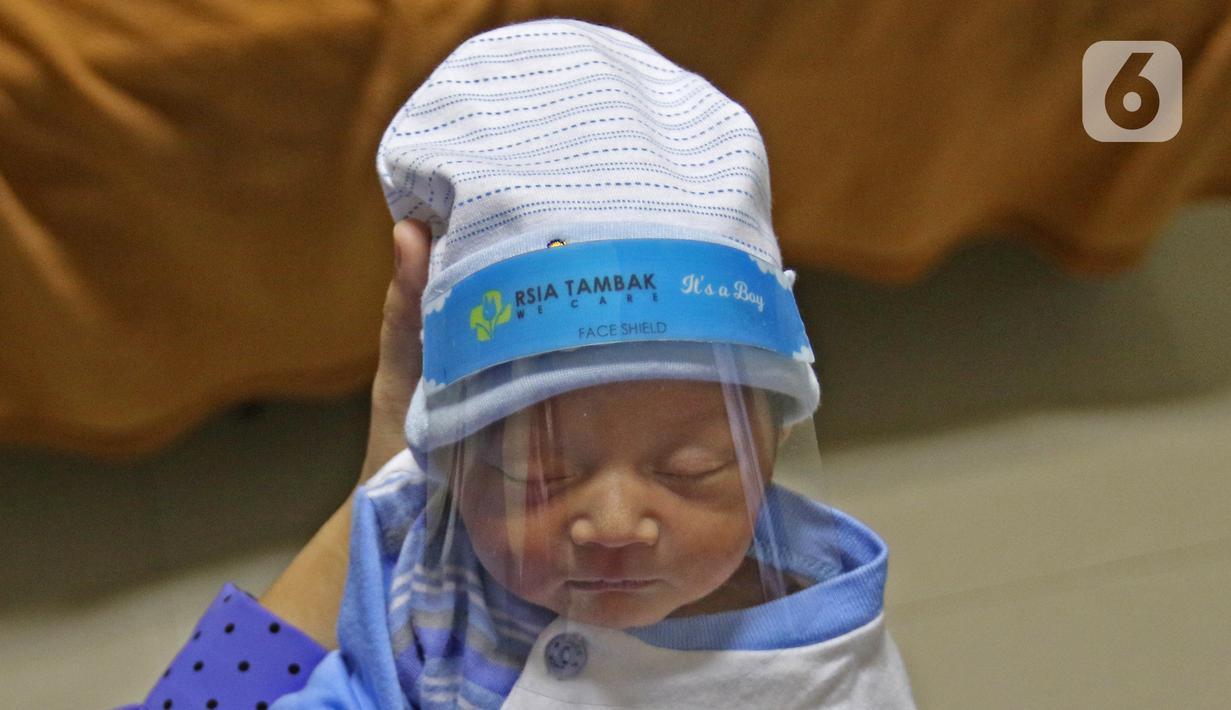 Seorang bayi memakai face shield atau pelindung wajah di Rumah Sakit Ibu dan Anak Tambak, Jakarta, Selasa (14/4/2020). RSIA Tambak sejak 12 April 2020 membuat kebijakan bayi yang baru lahir dipakaikan pelindung wajah untuk mencegah terpapar virus corona COVID-19. (Liputan6.com/Herman Zakharia)