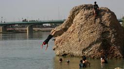 Anak-anak terjun dari reruntuhan bangunan tua ke Sungai Tigris untuk mendinginkan diri dari cuaca panas di Baghdad, Irak, Kamis (1/7/2021). Pemerintah Irak menetapkan 1 Juli 2021 sebagai hari libur resmi di Baghdad karena gelombang panas yang menyengat. (AP Photo/Khalid Mohammed)