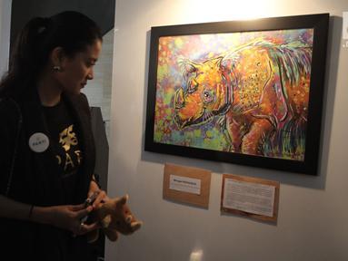 Artis Marcella Zalianty saat melihat karya dalam pameran seni badak Sumatera di Perpustakaan Nasional Indonesia, Jakarta Pusat, Jumat (19/1). Pameran ini bertajuk 'Harta Karun Tersembunyi Indonesia'. (Liputan6.com/Arya Manggala)
