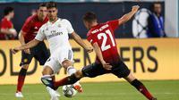 Gelandang Real Madrid Marco Asencio berusaha mengontrol bola dari kawalan pemain MU Ander Herrera saat bertanding pada International Champions Cup di Miami Gardens, Fla (31/7). MU menang tipis 2-1 atas Madrid. (AP Photo / Brynn Anderson )