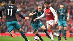 Striker Arsenal, Alex Iwobi, berusaha melewati kepungan pemain Southampton pada laga Premier League di Stadion Emirates, London, Minggu (8/4/2018). Arsenal menang 3-2 atas Southampton. (AFP/Glyn Kirk)