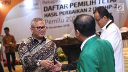 Ketua KPU Pusat, Arief Budiman (kiri) menyalami perwakilan partai politik peserta Pemilu 2019 jelang memimpin pleno Rekapitulasi Daftar Pemilih Tetap Hasil Perbaikan (DPTHP) 2 di Jakarta, Kamis (15/11).(Liputan6.com/Helmi Fithriansyah)