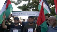 Warga Palestina di Kota Gaza pada 24 Juni 2019, mengibarkan bendera nasional dan memegang spanduk yang mengecam konferensi Perdamaian untuk Kemakmuran yang dipimpin AS di Bahrain. (MOHAMMED ABED / AFP)