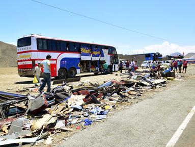 Puing-puing salah satu bus tampak berserakan di pinggir jalan tol Kota Huarmey, Peru, Senin (23/3/2015).  Insiden ini setidaknya menewaskan  34 orang tewas dan 70 luka-luka lainnya. (REUTERS/Toshiro Villanueva)