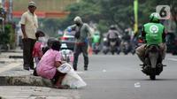 Pemulung duduk duduk di trotoar Jalan Margonda Raya, Depok, Kamis (16/4/2020). Pandemi COVID-19 memberikan dampak yang sangat besar bagi sosial dan ekonomi Indonesia. Bahkan yang paling dikhawatirkan bertambahnya angka kemiskinan dan pengangguran. (Liputan6.com/Helmi Fithriansyah)