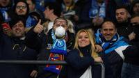 Seorang suporter Napoli mengenakan masker menunggu dimulainya pertandingan antara Napoli dan Barcelona di Stadion San Paolo di Naples, Italia, Selasa, (25/2/2020). Italia melaporkan kenaikan kasus infeksi virus Corona COVID- 91 menjadi lebih 272 kasus. (AFP Photo/Filippo Monteforte)