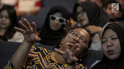 Relawan bisik menjelaskan alur cerita kepada tunanetra saat menyaksikan Bioskop Bisik di Pavilliun 28, Jakarta, Minggu (14/1). Hal ini membuat penyandang tunanetra dapat mengerti dan merasakan emosi yang ada di film tersebut. (Liputan6.com/Faizal Fanani)