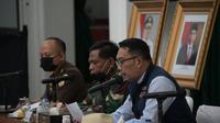 Gubernur Jawa Barat Ridwan Kamil tengah memimpin rapat koordinasi yang dilakukan secara telekonferensi dengan pemerintah pusat dan beberapa Gubernur, guna penanggulangan Covid-19. (Liputan6.com/Jayadi Supriadin)