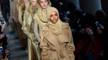 Model berhijab keturunan Amerika-Somalia, Halima Aden tampil di atas catwalk fashion show Max Mara women's Fall/Winter 2017-2018 dalam Milan Fashion Week, di Milan, Kamis (23/2). (Miguel MEDINA/AFP)