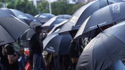 Peserta aksi melakukan aksi Kamisan di depan Istana Negara, Jakarta, Kamis (24/1). Mereka meminta pemerintah segera menuntaskan penyelesaian kasus pelanggaran HAM masa lalu dan membentuk pengadilan HAM. (Liputan6.com/Helmi Fithriansyah)