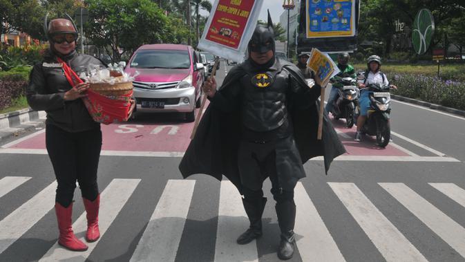 Warga mengenakan kostum superhero Gundala dan Batman saat melakukan aksi sosialisasi pencegahan virus corona di Solo, Rabu (4/3/2020). Aksi juga mengajak masyarakat menjaga kebersihan dan kesehatan dengan menerapkan pola hidup sehat. (AFP Photo/Anwar Mustafa)