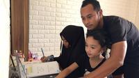 Atep saat jadi guru dadakan terhadap kedua putrinya. (Bola.com/Erwin Snaz)