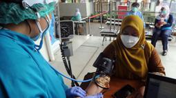 Dokter memeriksa kondisi seorang wanita sebelum melakukan vaksinasi virus corona COVID-19 produksi Sinovac di Puskemas Jagakarsa, Jakarta Selatan, Kamis (14/1/2020). Sejumlah Puskesmas di Jabodetabek mulai melakukan vaksinasi COVID-19 pada hari ini. (merdeka.com/Arie Basuki)