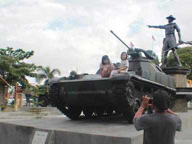 Pengunjung mengambil gambar anaknya di atas tank tempur bersejarah TNI yang berada di Monumen Nani Wartabone di Kilometer Nol Kota Gorontalo, Sabtu (22/9). Keberadaan dua tank tempur jadi buruan warga untuk berswafoto. (Liputan6.com/Arfandi Ibrahim)