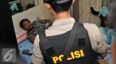 Petugas memeriksa WNA di apartemen Gading Nias, Jakarta, Kamis (1/9). Pemeriksaan yang dilakukan petugas Imigrasi, BNN, dan Polda Metro Jaya ini terkait pendataan WNA dan dugaan tindak pidana penyalahgunaan narkotika. (Liputan6.com/Gempur M Surya)