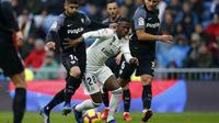 Striker Real Madrid, Vinicius JR, berusaha melewati pemain Sevilla pada laga La Liga di Stadion Santiago Bernabeu, Sabtu (19/1). Real Madrid menang 2-0 atas Sevilla. (AP/Andrea Comas)