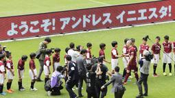 Pemain baru Vissel Kobe, Andres Iniesta menyalami anak-anak  sekolah sepak bola saat perkenalan di NOEVIR Stadium Kobe, Kobe, (26/5/2018). Iniesta dikontrak Vissel Kobe selama tiga tahun. (Yohei Nishimura/Kyodo News via AP)