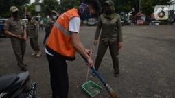 Warga yang tidak memakai masker melakukan sanksi menyapu jalan saat terjaring razia protokol kesehatan COVID-19 di Kebon Nanas, Jakarta, Selasa (15/6/2021). Saat kasus positif Covid-19 di Jakarta meningkat, masih banyak warga yang belum menjalankan protokol kesehatan. (merdeka.com/Imam Buhori)
