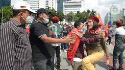Suasana saat massa gabungan dari berbagai elemen buruh dan organisasi mahasiswa berunjuk rasa memperingati Hari Buruh atau May Day di area Patung Kuda, Jakarta, Sabtu (1/5/2021). Polisi mengamankan sejumlah massa yang diduga mahasiswa dalam aksi unjuk rasa tersebut. (merdeka.com/Imam Buhori)