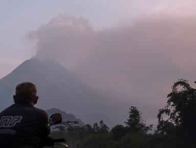 Seorang pria menyaksikan Gunung Merapi menyemburkan material vulkanik ke udara di Sleman, DI Yogyakarta, Selasa (3/3/2020). Gunung Merapi meletus pada pukul 05.22 WIB dengan tinggi kolom 6.000 meter , status waspada (level II). (AP Photo/Slamet Riyadi)