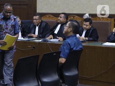 Mantan Kadis PU Papua, Mikael Kambuaya (kiri) dan Komisaris PT Manbers Jaya Mandiri, David Manibui saat sidang dakwaan di Pengadilan Tipikor Jakarta, Rabu (20/11/2019). Keduanya didakwa dalam kasus dugaan suap pekerjaan peningkatan jalan Kemiri-Depapre TA 2015. (Liputan6.com/Helmi Fithriansyah)