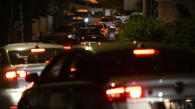 Sejumlah mobil polisi menuju rumah mantan Perdana Menteri Malaysia, Najib Razak di Kuala Lumpur, Rabu (16/5). Polisi melakukan penggeledahan di kediaman Najib usai Salat Tarawih untuk mencari bukti dan dokumen terkait kasus 1MDB. (AFP/Mohd RASFAN)