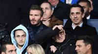 Mantan bintang sepak bola David Beckham (kiri) dan Gary Neville menonton pertandingan Liga Champions antara PSG dan Real Madrid di stadion Parc des Princes di Paris (6/3). (AFP Photo/Franck Fife)