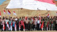 Bendera merah putih ukuran raksasa dikibarkan masyarakat, Polri dan TNI di wilayah perbatasan RI-RDTL, Rabu (16/8/2018).