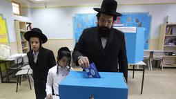 Anak-anak menyaksikan pria Yahudi ultra-Ortodoks memberikan suaranya selama pemilihan parlemen Israel di Yerusalem (9/4). Warga Israel hari ini memberikan suara dalam pemilihan tingkat tinggi yang akan memutuskan masa jabatan PM Benjamin Netanyahu. (AFP Photo/Menahem Kahana)
