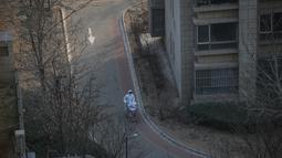 Seorang staf dengan alat pelindung diri mengangkut suplai dengan troli di Distrik Daxing di Beijing, ibu kota China, pada 20 Januari 2021. Distrik Daxing akan memberlakukan manajemen lockdown ketat di lima kompleks permukiman di subdistrik Tiangongyuan di mana kasus-kasus baru itu terdeteksi. (Xinhu