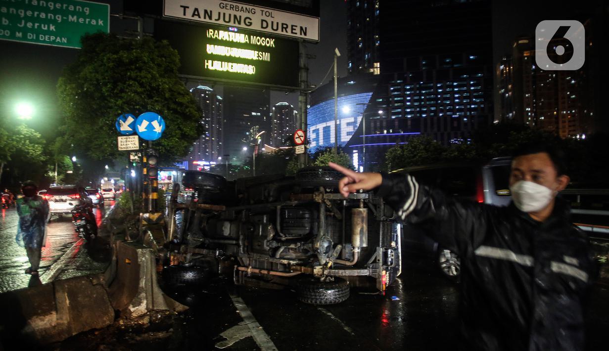Sebuah mobil jenis jeep terguling di depan gerbang Tol Tanjung Duren, Jalan S Parman, Jakarta Barat, Minggu (26/9/2021). Tidak ada korban jiwa, namun kecelakaan tersebut membuat lalu lintas di jalan itu terimbas kemacetan yang cukup panjang. (Liputan6.com/Johan Tallo)