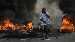 Demonstran berdiri dekat kobaran api saat menuntut keadilan atas pembunuhan Presiden Haiti Jovenel Moise di Cap-Haitien, Haiti, Kamis (22/7/2021). Demonstrasi menuntut keadilan atas pembunuhan Presiden Haiti Jovenel Moise terus berlanjut dan menimbulkan kerusuhan. (AP Photo/Matias Delacroix)