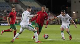 Pemain Portugal Cristiano Ronaldo (tengah) menggiring bola saat melawan Irlandia pada pertandingan kualifikasi grup A Piala Dunia 2022 di Stadion Algarve, luar Faro, Portugal, Rabu (1/9/2021). Ronaldo mencetak dua gol saat Portugal menang 2-1. (AP Photo/Armando Franca)