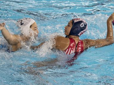Pemain polo air putri Indonesia, Nyoman Ayu, mengamankan bola dari pemain polo air Jepang pada laga Asian Games di Aquatic Center, GBK, Jakarta, Kamis (16/8/2018). Jepang menang 15–4 atas Indonesia. (Bola.com/Vitalis Yogi Trisna)