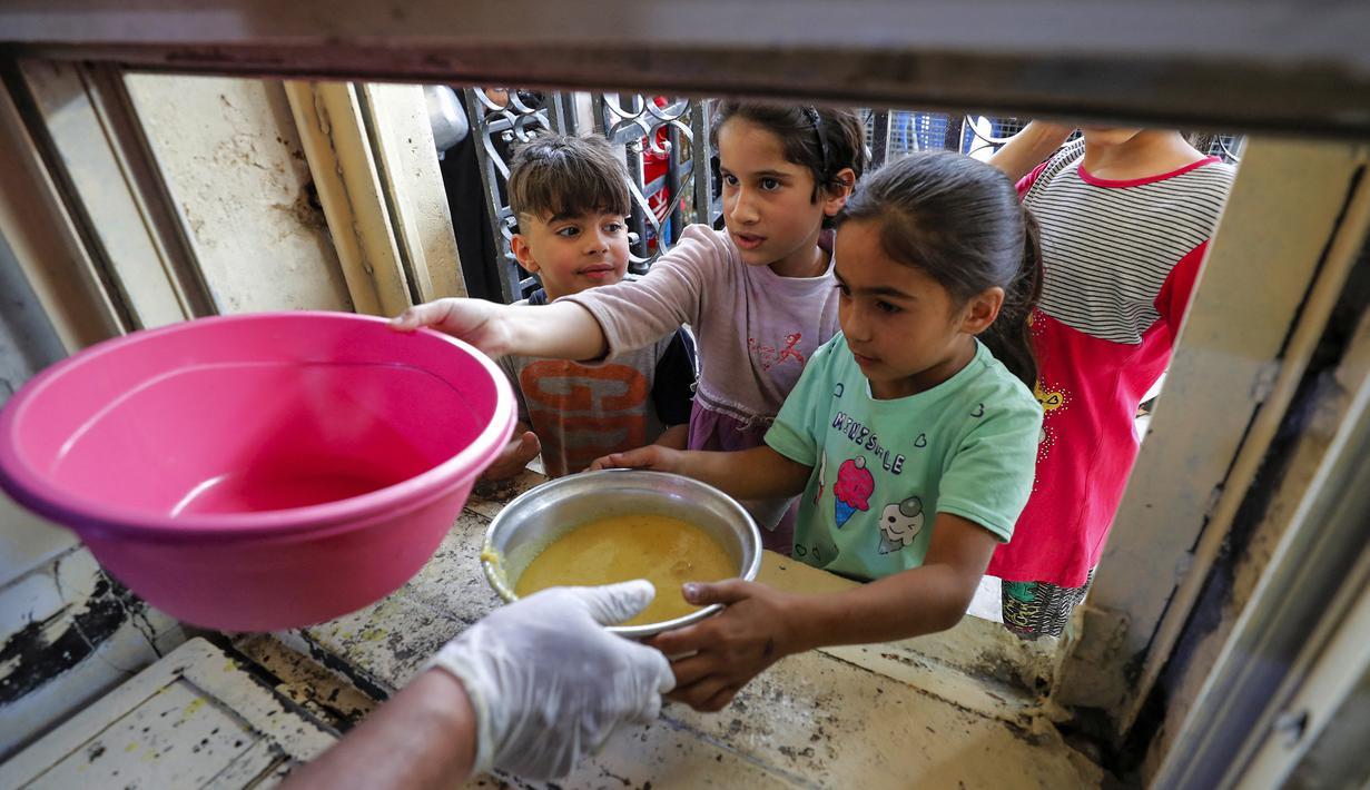 Anak-anak yang membutuhkan menerima makanan berbuka puasa dari juru masak di dapur Masjid Muslim Sunni Abdel Kader al-Kilani, Baghdad, Irak, 19 April 2021. Kegiatan ini berlangsung selama bulan suci Ramadhan. (AHMAD AL-RUBAYE/AFP)