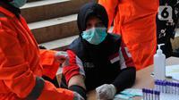 Seorang tenaga kesehatan medis melakukan rapid test pendektesian COVID-19 di Stadion Patriot Candrabhaga, Bekasi, Jawa Barat, Rabu (25/3/2020). Pemeriksaan itu khusus hanya diperuntukan bagi tenaga medis seluruh puskesmas, dan rumah sakit yang ada di Kota Bekasi. (Liputan6.com/Herman Zakharia)