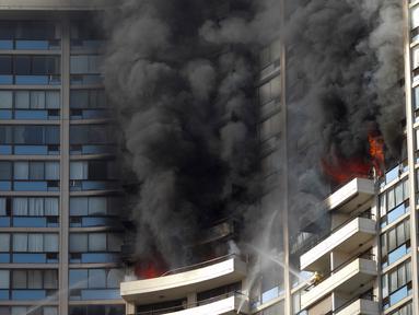 Petugas pemadam kebakaran menyemprotkan air untuk memadamkan api saat terjadi kebakaran di apartemen Marco Polo, Honolulu (14/7). Setidaknya tiga orang tewas akibat kebakaran yang terjadi di apartemen tersebut. (AP Photo / Marco Garcia)