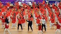 Menko PMK, Puan Maharani (tengah jaket hitam) bersama sejumlah atlet, pelatih dan official menari lagu tema Asian Games 2018 usai upacara pengukuhan di Istora Senayan, Jakarta, Minggu (5/8). (Liputan6.com/Helmi Fithriansyah)