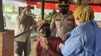 Kapolsek Sawangan AKP Muhammad Melta Mubarak, menenangkan warga yang takut jarum suntik vaksin Covid-19 dalam vanksinasi Bhara Daksa Akpol 91 di Kota Depok. (Liputan6.com/Dicky Agung Prihanto)
