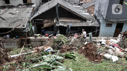 Warga membersihkan puing reruntuhan bangunan pascatanah longsor di kawasan Kemang Timur XI, Jakarta Selatan, Minggu (21/2/2021). Longsor terjadi akibat derasnya arus kali yang kemudian bangunan menimpa permukiman warga di bawahnya. (merdeka.com/Iqbal S. Nugroho)