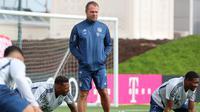 Pelatih Bayern Muenchen, Hansi Flick, mengamati anak asuhnya saat latihan Senin (6/4/2020). Pemuncak klasemen sementara liga Jerman ini berlatih bersama untuk pertamakalinya sejak Bundesliga dihentikan pada 13 Maret karena virus corona. (AFP/Christof Stache)