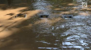 Sejumlah makam terendam banjir di kampung Arus Cawang, Jakarta Timur, Jumat (26/4). Ketinggan banjir kurang lebih satu meter terjadi akibat luapan kali Ciliwung dan intensitas curah hujan di kawasan Bogor Jawa Barat sangat tinggi sehingga aktivitas warga terhambat. (merdeka.com/Imam Buhori)