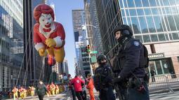 Polisi berjaga saat Balon Ronald McDonald memeriahkan parade Hari Thanksgiving di Manhattan, New York, AS (23/11). Peringatan 'Thanksgiving' merupakan Hari Pengucapan Syukur di akhir musim panen. (AP Photo/Mary Altaffer)