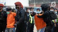 Anggota Densus 88 Antiteror menggiring terduga teroris saat tiba di Bandara Soekarno-Hatta, Tangerang, Banten, Kamis (18/3/2021). Polri memindahkan 22 terduga teroris jaringan kelompok Jamaah Islamiyah (JI) dari Jawa Timur ke Jakarta. (merdeka.com/Imam Buhori)