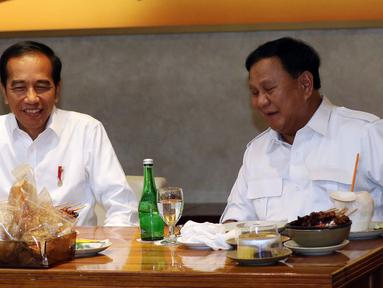 Presiden terpilih Joko Widodo atau Jokowi (kiri) makan siang bersama Ketua Umum Partai Gerindra Prabowo Subianto di FX Sudirman, Jakarta, Sabtu (13/7/2019). Jokowi dan Prabowo terlihat penuh tawa saat menyantap sate dan kelapa muda. (Liputan6.com/JohanTallo)