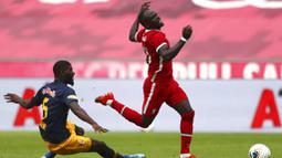 Pemain Liverpool, Sadio Mane, terjatuh saat berebut bola dengan pemain RB Salzburg, Jerome Onguene, pada laga persahabatan di Stadion Red Bull Arena, Salzburg, Selasa (25/8/2020). Kedua tim bermain imbang dengan skor 2-2. (AP Photo/Matthias Schrader)