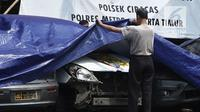 Petugas melihat melihat kondisi mobil yang dirusak di Polsek Ciracas, Jakarta, Rabu (12/12). Pelayanan di Polsek Ciracas lumpuh pascapembakaran oleh massa. (Liputan6.com/Herman Zakharia)