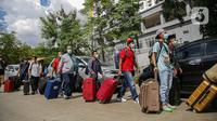 Warga negara Indonesia (WNI) membawa koper mereka usai menjalani isolasi di RSDC Wisma Atlet Pademangan, Jakarta, Selasa (15/6/2021). Pemerintah mewajibkan WNI yang baru tiba di Indonesia untuk melakukan isolasi selama lima hari guna menghindari penularan COVID-19. (Liputan6.com/Faizal Fanani)