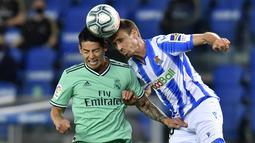 Pemain Real Madrid, James Rodriguez, duel udara dengan pemain Real Sociedad, Nacho Monreal, pada laga La Liga di Reale Seguros Stadium, Minggu (21/6/2020). Real Madrid menang 2-1 atas Real Sociedad. (AP Photo/Alvaro Barrientos)